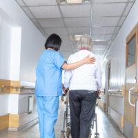 Asian doctor helping elder woman with walker in hospital hallway