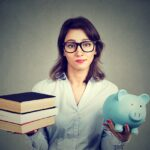 Young woman with stack pile of books and piggy bank full of debt rethinking future career path